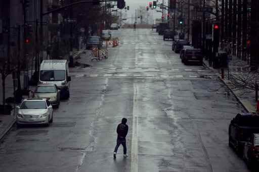FILE - In this April 3, 2020, file photo a man crosses an empty street in downtown Kansas City, Mo. Americans are increasingly taking preventative measures, including staying away from large crowds and avoiding touching their hands to their faces, amid growing fears of infection with COVID-19, a new poll from The Associated Press-NORC Center for Public Affairs Research found. (AP Photo/Charlie Riedel, File)