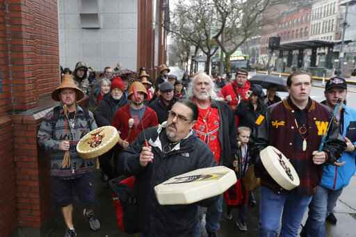 FILE - In this Jan. 6, 2020, file photo, Tony A. (Naschio) Johnson, center, elected chairman of the Chinook Indian Nation, plays a drum as he leads tribal members and supporters as they march to the federal courthouse in Tacoma, Wash., as they continue their efforts to regain federal recognition. As COVID-19 disproportionately affects Native American communities, many tribal leaders say the pandemic poses particular risks to tribes without federal recognition. The Chinook Nation received some federal funding through a local nonprofit for small tribes to distribute food to elders and help with electricity bills, tribal Johnson said. (AP Photo/Ted S. Warren, File)