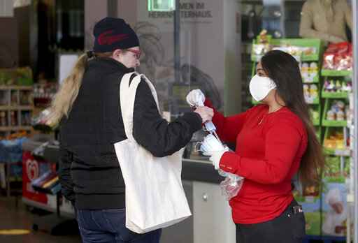 Supermarket employees distribute protective masks to customers in Vienna, Austria, Wednesday, April 1, 2020. In Austria protective masks should be worn in shops from Wednesday on. The Austrian government has moved to restrict freedom of movement for people, in an effort to slow the onset of the COVID-19 coronavirus. The new coronavirus causes mild or moderate symptoms for most people, but for some, especially older adults and people with existing health problems, it can cause more severe illness or death. (AP Photo/Ronald Zak)
