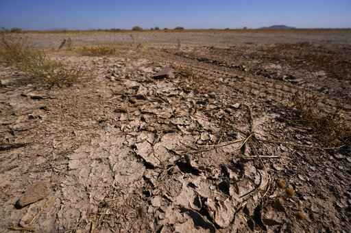 FILE - In this Wednesday, Sept. 30, 2020 file photo, dry desert soil cracks due to the lack of monsoon rainfall in Maricopa, Ariz. In a report released on Thursday, Oct. 15, 2020, National Oceanic and Atmospheric Administration forecasters see a dry winter for all of the south from coast-to-coast and say that could worsen an already bad drought. (AP Photo/Ross D. Franklin)