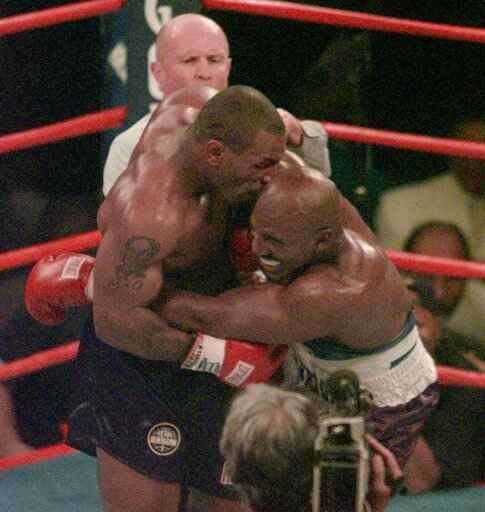 FILE - This June 28, 1997, file photo shows Mike Tyson biting into the ear of Evander Holyfield in the third round of their WBA heavyweight match in Las Vegas. Violence is part of the game in many sports. But when the Cleveland�s Myles Garrett ripped the helmet off Mason Rudolph and hit the Pittsburgh Steelers� quarterback in the head with it, the Browns� defender crossed a line _ one that attracts the attention of authorities sometimes from within their sport and in other cases from criminal prosecutors.(AP Photo/Jack Smith, File)