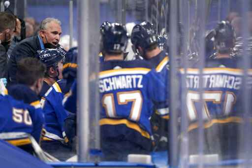 St. Louis Blues head coach Craig Berube, left, talks with his team during the second period of an NHL hockey game against the Vegas Golden Knights Monday, April 5, 2021, in St. Louis. (AP Photo/Jeff Roberson)