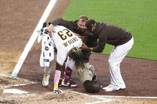 San Diego Padres manger Jayce Tingler, right, and a trainer, center back, help Fernando Tatis Jr. (23) to his feet after Tatis hurt his shoulder while swinging at a pitch in the third inning of a baseball game against the San Francisco Giants, Monday, April 5, 2021, in San Diego. (AP Photo/Derrick Tuskan)