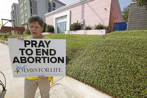 FILE - In this Oct. 2, 2019 file photo, an abortion opponent sings to herself outside the Jackson Womens Health Organization clinic in Jackson, Miss. Three judges from a conservative federal appeals court are hearing arguments, Monday, Oct. 7,  over a Mississippi law that would ban most abortions after 15 weeks of pregnancy.  Republican Gov. Phil Bryant signed the law in 2018, the state's only abortion clinic immediately sued and U.S. District Judge Carlton Reeves blocked the law from taking effect.  (AP Photo/Rogelio V. Solis)