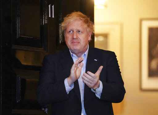 FILE - In this Thursday, April 2, 2020 handout photo provided by 10 Downing Street, Britain's Prime Minister Boris Johnson claps outside 11 Downing Street to salute local heroes during Thursday's nationwide Clap for Carers NHS initiative to applaud workers fighting the coronavirus pandemic, in London. British Prime Minister Boris Johnson has been admitted to a hospital with the coronavirus. Johnson's office says he is being admitted for tests because he still has symptoms 10 days after testing positive for the virus. (Pippa Fowles/10 Downing Street via AP, File)