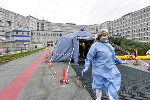 FILE - In this Feb. 29, 2020 file photo, a paramedic walks out of a tent that was set up in front of the emergency ward of the Cremona hospital, northern Italy. Italian doctors celebrated one small victory in their battle against the coronavirus Monday after Patient No. 1, a 38-year-old named Mattia was moved out of intensive care. But in the rest of hard-hit northern Italy, the virus' spread was growing so exponentially that doctors spoke of choices war-time triage medics make in deciding who lives and who dies, and who get access to the limited number of ICU beds. (Claudio Furlan/Lapresse via AP, file)