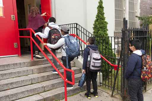 A teacher leads her students into an elementary school in the Brooklyn borough of New York on Tuesday, Sept. 29, 2020, as hundreds of thousands of elementary school students are heading back to classrooms in the city, resuming in-person learning during the coronavirus pandemic. The coronavirus is infecting a rising number of American children and teens in a trend authorities say appears driven by school reopenings and the resumption of sports, playdates and other activities. (AP Photo/Mark Lennihan)
