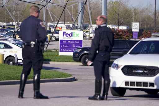 Police stand near the scene where multiple people were shot at the FedEx Ground facility early Friday morning, April 16, 2021, in Indianapolis. A gunman killed eight people and wounded several others before apparently taking his own life in a late-night attack at a FedEx facility near the Indianapolis airport, police said, in the latest in a spate of mass shootings in the United States after a relative lull during the pandemic. (AP Photo/Michael Conroy)