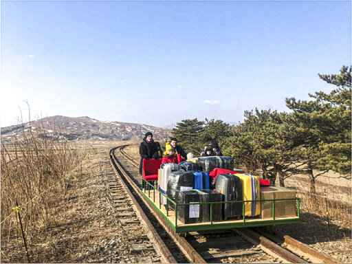 In this image taken from a video released by Russian Foreign Ministry Press Service Thursday, Feb. 25, 2021, a group of Russian diplomats push hand-pushed rail trolley with their children and suitcases to the border with Russia. A group of Russian diplomats and their family members returned to Russia from North Korea on a hand-pushed rail trolley on Thursday because of COVID-19 restrictions in the country, Russia's Foreign Ministry said in a Facebook post. (Russian Foreign Ministry Press Service via AP)