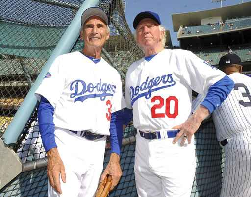 This June 8, 2013, photo shows Hall of Fame and former Los Angeles Dodgers pitcher Don Sutton, right, and Brooklyn Dodger pitcher Sandy Koufax, left, during the Old-Timers game prior to a baseball game between the Atlanta Braves and the Los Angeles Dodgers in Los Angeles. Sutton, a Hall of Fame pitcher who spent most of his career in a Los Angeles Dodgers' rotation that included Koufax and Don Drysdale, has died, Tuesday, Jan. 19, 2021. He was 75. (Keith Birmingham/The Orange County Register via AP, File)