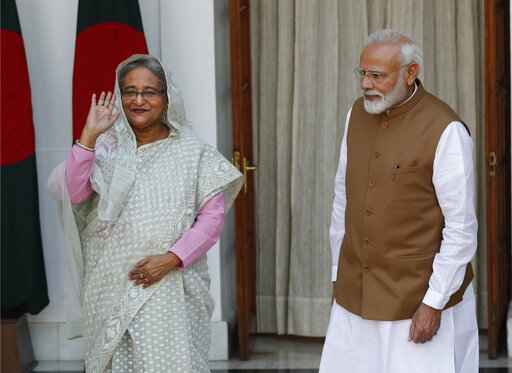 Indian Prime Minister Narendra Modi, right, watches his Bangladeshi counterpart Sheikh Hasina wave to the media before their meeting in New Delhi, India, Saturday, Oct. 5, 2019. Hasina arrived in India on Thursday for a visit during which she is expected to sign agreements on increasing trade and investment and improving regional connectivity. (AP Photo/Manish Swarup)