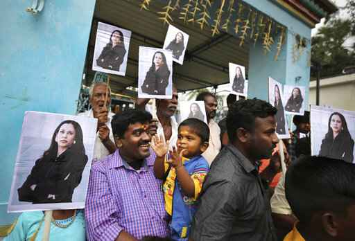 A child reacts as villagers hold placards featuring U.S. Vice President-elect Kamala Harris after participating in special prayers ahead of her inauguration, outside a Hindu temple in Thulasendrapuram, the hometown of Harris' maternal grandfather, south of Chennai, Tamil Nadu state, India, Wednesday, Jan. 20, 2021. A tiny, lush-green Indian village surrounded by rice paddy fields was beaming with joy Wednesday hours before its descendant, Kamala Harris, takes her oath of office and becomes the U.S. vice president. (AP Photo/Aijaz Rahi)