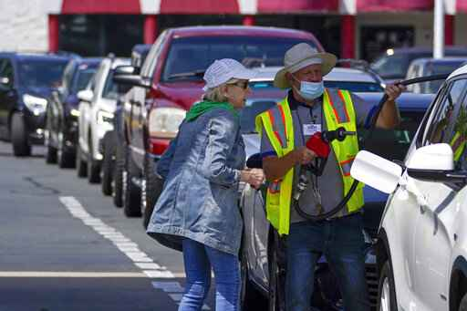 A customer helps pumping gas at Costco, as other wait in line, on Tuesday, May 11, 2021, in Charlotte, N.C. Colonial Pipeline, which delivers about 45% of the fuel consumed on the East Coast, halted operations last week after revealing a cyberattack that it said had affected some of its systems. (AP Photo/Chris Carlson)
