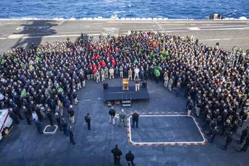 FILE - In this Dec. 15, 2019, file photo, U.S.Navy Capt. Brett Crozier, commanding officer of the aircraft carrier USS Theodore Roosevelt (CVN 71), addresses the crew during an all hands call on the ship's flight deck while conducting routine training in the Eastern Pacific Ocean. The commander of the U.S. 7th Fleet visited the leadership of the USS Theodore Roosevelt in Guam, where the aircraft carrier is being cleaned after an outbreak of COVID-19 among its crew. The ship's commander, Capt. Crozier, was fired for going outside of the chain of command in asking for help for the outbreak, in a decision now under review. (U.S. Navy Photo by Mass Communication Specialist Seaman Kaylianna Genier via AP)
