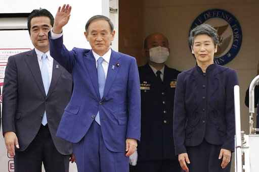 Japan's Prime Minister Yoshihide Suga, second left, and his wife Mariko prepare to leave Haneda airport in Tokyo Sunday, Oct. 19, 2020. Suga left Sunday on his first overseas foray since taking over from his former boss Shinzo Abe last month, heading to Vietnam and Indonesia. (Shigeyuki Inakuma/Kyodo News via AP)