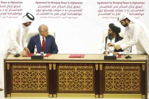 FILE - In this Feb. 29, 2020 file photo, U.S. peace envoy Zalmay Khalilzad, left, and Mullah Abdul Ghani Baradar, the Taliban group's top political leader sign a peace agreement between Taliban and U.S. officials in Doha, Qatar. The Taliban in a statement Sunday, April 5, 2020, said  that a peace deal they signed with the United States is near breaking point accusing Washington of violations that included drone attacks on civilians, while chastising the Afghan government for dithering on the release of 5,000 Taliban prisoners, promised in the agreement. (AP Photo/Hussein Sayed, File)