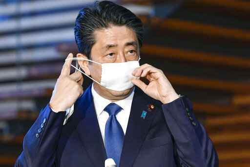 Japanese Prime Minister Shinzo Abe takes off mask as he speaks to reporters at the prime minister's official residence in Tokyo Monday, April 6, 2020. Abe said that he will declare a state of emergency for Tokyo and six other prefectures as early as Tuesday, April 7, to bolster measures to fight the coronavirus outbreak, but that there will be no hard lockdowns.(Yoshitaka Sugawara/Kyodo News via AP)