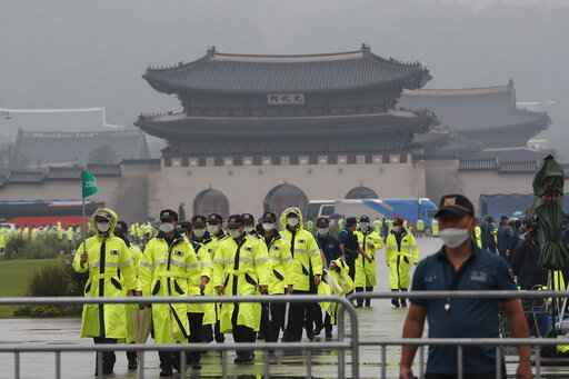 Police officers wearing face masks to help protect against the spread of the coronavirus patrol around the Gyeongbok Palace, one of South Korea's well-known landmarks, in Seoul, South Korea, Saturday, Aug. 15, 2020. (AP Photo/Ahn Young-joon)