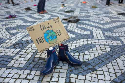 Pairs of shoes with messages about environment protection are placed by activists evenly spaced over a square in Lisbon during a global climate protest, Friday, Sept. 25, 2020. (AP Photo/Armando Franca)