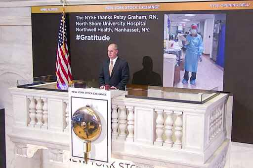 In this photo taken from video provided by the New York Stock Exchange, Chief Security Officer Kevin Fitzgibbons rings the opening bell at the NYSE, Monday, April 6, 2020, recognizing Patsy Graham, a registered nurse at North Shore University Hospital Northwell Health, in Manhasset, NY. Stocks jumped in markets around the world Monday after some of the hardest-hit areas offered sparks of hope that the worst of the coronavirus outbreak may be on the horizon.  (New York Stock Exchange via AP)