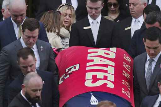 Julie Frates carries her daughter Lucy as they follow the casket of her husband Pete Frates following his funeral at St. Ignatius of Loyola Parish church at Boston College in Boston, Friday, Dec. 13, 2019. Frates, a former college baseball player whose determined battle with Lou Gehrig's disease helped inspire the ALS ice bucket challenge that has raised more than $200 million worldwide. (AP Photo/Charles Krupa)