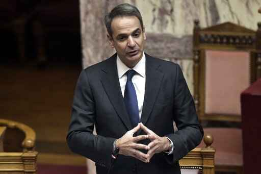 Greece's Prime Minister Kyriakos Mitsotakis speaks during a Parliament debate in Athens, Wednesday, Jan. 20, 2021. Lawmakers in Greece are set to approve legislation to extend the country's territorial waters along its western coastline from six to 12 nautical miles. (Giorgos Zachos/InTime News via AP)