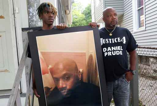 FILE - In this Sept. 3, 2020, file photo, Joe Prude, right, brother of Daniel Prude, and Daniel's nephew Armin, stand with a picture of Daniel Prude in Rochester, N.Y. In a decision announced Tuesday, Feb. 23, 2021, a grand jury voted not to charge officers shown on body camera video holding Daniel Prude down naked and handcuffed on a city street last winter until he stopped breathing. Joe Prude said Wednesday, Feb. 24 he had viewed police body camera footage showing what happened after officers caught up with Daniel Prude, naked on a frigid March night, as irrefutable proof of a crime. (AP Photo/Ted Shaffrey, File)