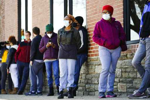 FILE - In this March 29, 2021, file photo, people wearing face masks as a precaution against the coronavirus wait in line to receive COVID-19 vaccines at a site in Philadelphia. Nearly half of new coronavirus infections nationwide are in just five states, including Pennsylvania - a situation that puts pressure on the federal government to consider changing how it distributes vaccines by sending more doses to hot spots. (AP Photo/Matt Rourke, File)