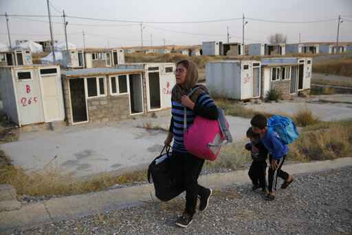 FILE - In this Oct. 17, 2019 file photo, Salwa Hanna with her children, who are newly displaced by the Turkish military operation in northeastern Syria, carry their belongings after they arrive at the Bardarash refugee camp, north of Mosul, Iraq,   For months, every time Turkey threatened to invade northern Syria, Salwa Hanna told her husband they should take their children and flee from the border town of Kobani. And every time, he told her not to worry, because the Americans were there. Now the Christian family is among an estimated 160,000 Syrians who have fled Turkey's offensive, which began last week after President Donald Trump announced he would move U.S. forces out of the way, abandoning their Kurdish allies.  (AP Photo/Hussein Malla)