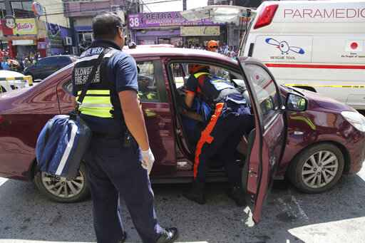 In this Oct. 18, 2019, handout photo provided by the Olongapo Public Information Office, rescue workers check on an Australian named Anthony George inside a car in Olongapo, northern Philippines. Philippine police city director of Olongapo city said they arrested Australian Michael McLaren shortly after the incident for the alleged killing of George and Filipino Mila Bailey inside the car. Another Australian victim, Wayne Bailey, is still recovering at the hospital from gunshot wounds. (Olongapo Public Information Office via AP)