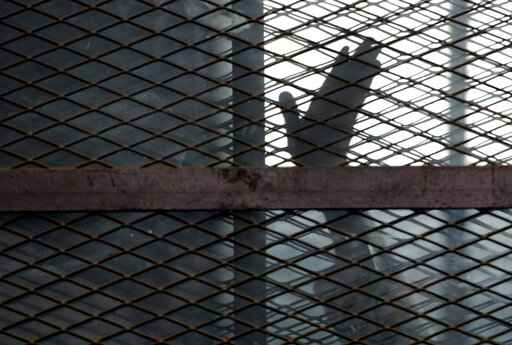 FILE - In this Aug. 22, 2015, file photo, a member of the Muslim Brotherhood waves his hand from a defendants cage in a courtroom in Torah prison, southern Cairo, Egypt. A report released by Amnesty International Wednesday, April 21, 2021, said the number of executions worldwide in 2020 plummeted to its lowest level in at least a decade. But the report said four states in the Middle East - Iran, Egypt, Iraq and Saudi Arabia respectively - topped the global list and pressed on with shootings, beheadings and hangings, ignoring pleas by rights groups to halt executions during the pandemic. (AP Photo/Amr Nabil, File)