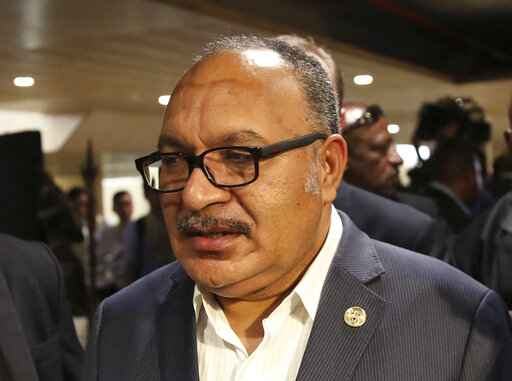 FILE - In this Nov. 18, 2018, file photo, Papua New Guinea's Prime Minister Peter O'Neill is chased by reporters after reading his statement at the end of the APEC 2018 summit at Port Moresby, Papua New Guinea. O'Neill was arrested Saturday, May 23, 2020 and taken in for questioning over misappropriation and corruption involving the purchase of two generators from Israel. O'Neill was arrested by police at Jackson's International Airport in Port Moresby after flying back from Brisbane,  Australia, where he had been stranded because of COVID-19 lockdowns. He was later released on bail and will spend two weeks in isolation at his home due to the same virus restrictions. (AP Photo/Aaron Favila)