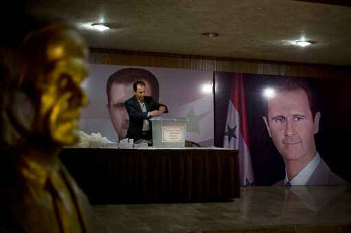 FILE - In this April 13, 2016 file photo, a Syrian election official waits for voters at a polling station with posters of President Bashar Assad during the parliamentary election in Damascus, Syria. On Sunday, April 18, 2021, Syria's parliament speaker announced that presidential elections in the war-ravaged country will be held May 26. The election is widely expected to give Assad a fourth seven-year term. (AP Photo/Hassan Ammar, File)