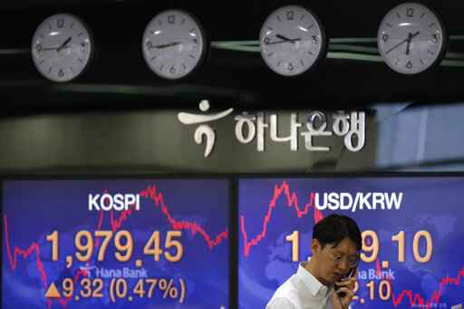 A currency trader talks on the phone near the screens showing the Korea Composite Stock Price Index (KOSPI), left, and the foreign exchange rate between U.S. dollar and South Korean won at the foreign exchange dealing room in Seoul, South Korea, Monday, May 25, 2020. Asian shares are mostly higher, with Tokyo stocks gaining on expectations that a pandemic state of emergency will be lifted for all of Japan. But shares fell in Hong Kong on Monday after police used tear gas to quell weekend protests over a proposed national security bill for the former British colony. (AP Photo/Lee Jin-man)