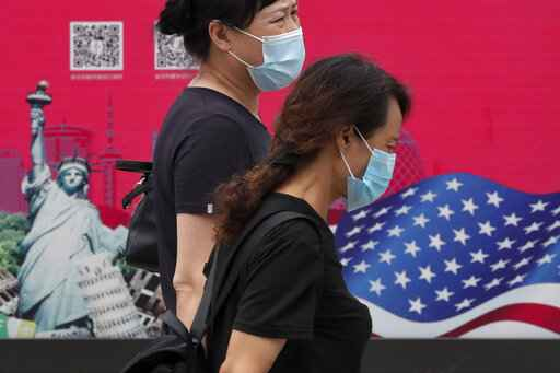 Women wearing face masks to help protect against the coronavirus walks by an advertising board displaying an American flag and Statue of Liberty on a street in Beijing, Thursday, Aug. 6, 2020. China's biggest recent outbreak of coronavirus has grown slightly. Hundreds people have developed COVID-19 in the far northwestern region of Xinjiang, with more than dozens of new cases reported Thursday in its capital and largest city, Urumqi. (AP Photo/Andy Wong)