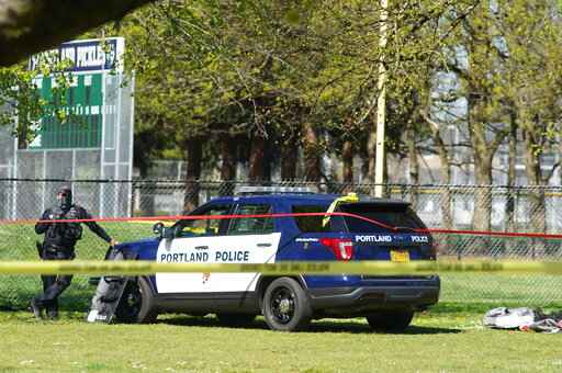 A Portland Police officer stand by following a police involved shooting of a man at Lents Park, Friday, April 16, 2021, in Portland, Ore. Police fatally shot a man in the city park Friday morning after responding to reports of a person with a gun, authorities said. (Beth Nakamura/The Oregonian/The Oregonian via AP)