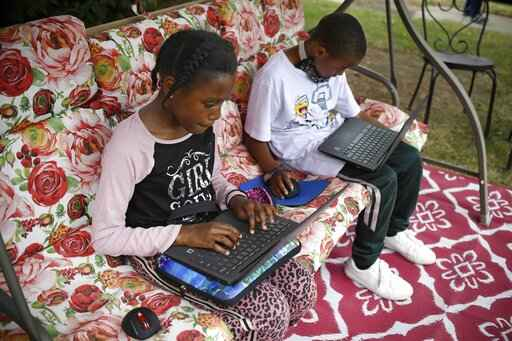 FILE - In this Friday June 5, 2020, file photo, fourth-grader Sammiayah Thompson, left, and her brother, third-grader Nehemiah Thompson, work outside in their yard on laptops provided by their school system for distant learning in Hartford, Conn. Americans can begin applying for $50 off their internet bill on Wednesday, May 12, 2021, as part of an emergency government program to keep people connected during the pandemic. (AP Photo/Jessica Hill, File)