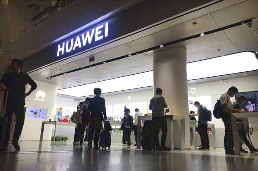 FILE - In this Nov. 15, 2019, file photo people look at a Huawei store in Shenzhen Bao'an International Airport in Shenzhen in southern China's Guangdong Province. A federal judge in Texas has dismissed Chinese tech giant Huawei's lawsuit challenging a U.S. law that bars the government and its contractors from using Huawei equipment because of security concerns. (AP Photo/Olivia Zhang, File)