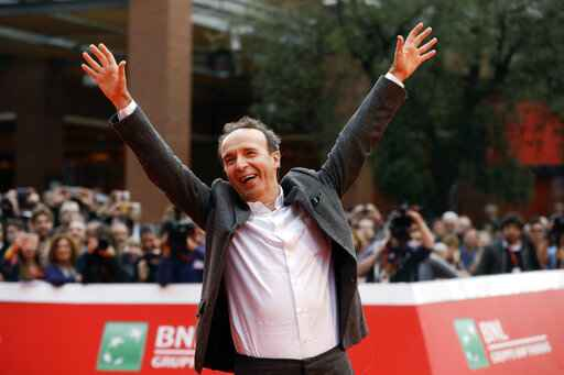 FILE - In this Sunday, Oct. 23, 2016 filer, Roberto Benigni poses for photographers as he arrives on the red carpet at the Rome Film Festival. The Venice Film Festival said Thursday, April 15, 2021 it will give its lifetime achievement award this year to Oscar-winning director and actor Roberto Benigni. The Golden Lion for Lifetime Achievement is to be awarded at 78th edition of the world's oldest film festival, scheduled for Sept. 1-11 on the Lido. Benigni wrote, directed and starred in