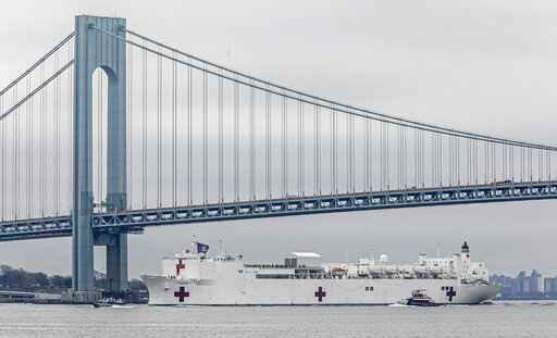 CORRECTS BYLINE TO BEBETO MATTHEWS, NOT SETH WENIG - The Navy hospital ship USNS Comfort passes under the Verrazzano-Narrows Bridge on its way to docking in New York, Monday, March 30, 2020. The ship has 1,000 beds and 12 operating rooms that could be up and running within 24 hours of its arrival on Monday morning. It's expected to bolster a besieged health care system by treating non-coronavirus patients while hospitals treat people with COVID-19. (AP Photo/Bebeto Matthews)