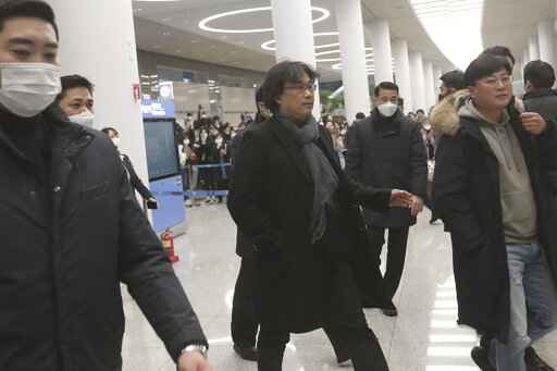 South Korean director Bong Joon-ho, center, arrives at the Incheon International Airport in Incheon, South Korea, Sunday, Feb. 16, 2020. South Koreans are reveling in writer-director Bong's dark comic thriller,