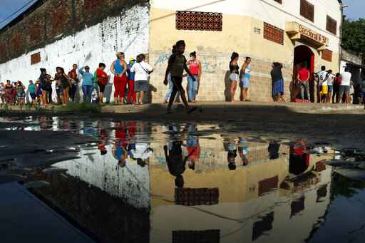 FILE - In this Tuesday, March 31, 2020 file photo, neighbors line up for free food staples outside Santa Ana primary school in Asuncion, Paraguay, part of an already existing food program through the Education Ministry, as people stay home from work amid the spread of the COVID-19 coronavirus. According to research released on Wednesday, April 1, 2020, more evidence is emerging that coronavirus infections are being spread by people who have no clear symptoms, complicating efforts to gain control of the pandemic. (AP Photo/Jorge Saenz)