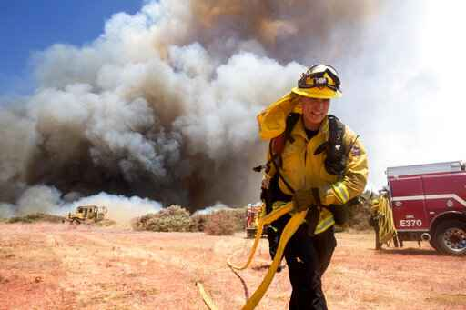 A firefighter battles a brush fire at the Apple Fire in Cherry Valley, Calif., Saturday, Aug. 1, 2020. A wildfire northwest of Palm Springs flared up Saturday afternoon, prompting authorities to issue new evacuation orders as crews fought the blaze in triple-degree heat. The blaze began as two separate fires Friday evening in Cherry Valley, an unincorporated area near the city of Beaumont in Riverside County. (AP Photo/Ringo H.W. Chiu)