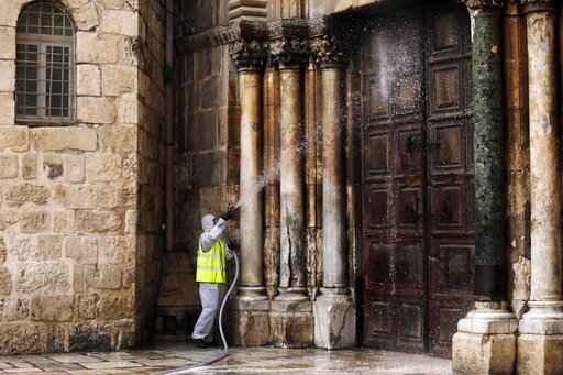 A worker disinfects the doors of the closed Church of the Holy Sepulchre in Jerusalem's Old City, as general public movements are limited to prevent the spread of coronavirus, Monday, March 30, 2020. (AP Photo/Mahmoud Illean)