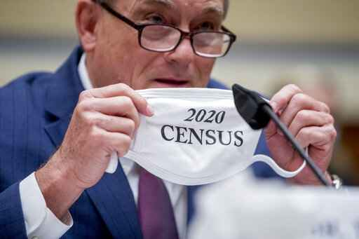 Census Bureau Director Steven Dillingham holds up his mask with the words