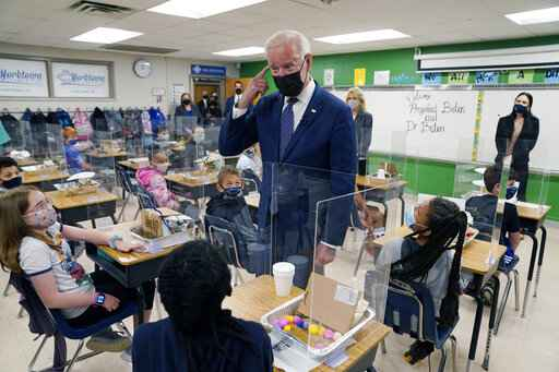 In this May 3, 2021, photo, President Joe Biden gestures as he talks to students during a visit to Yorktown Elementary School, in Yorktown, Va., as first lady Jill Biden watches. Biden has met his goal of having most elementary and middle schools open for full, in-person learning in his first 100 days. (AP Photo/Evan Vucci)
