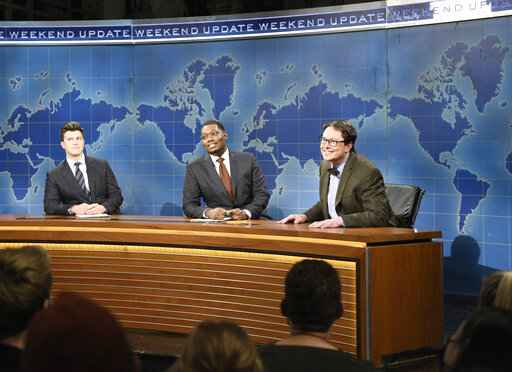 This image released by NBC shows, from left, Colin Jost, Michael Che, and host Elon Musk as financial expert Lloyd Ostertag during the