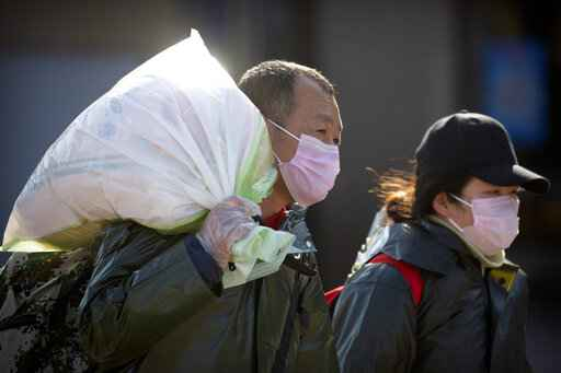Travelers wear face masks as they walk outside the Beijing Railway Station in Beijing, Saturday, Feb. 15, 2020. People returning to Beijing will now have to isolate themselves either at home or in a concentrated area for medical observation, said a notice from the Chinese capital's prevention and control work group published by state media late Friday. (AP Photo/Mark Schiefelbein)