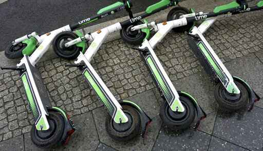 FILE - In this Friday, Sept. 13, 2019 file photo, electric rental scooters lie on a sidewalk in Berlin, Germany. Britain is giving the green light for trials of electric scooter rental programs, as authorities look for ways to help people get moving while maintaining distance and easing pressure on public transit. The transport department on Tuesday, June 30, 2020 unveiled new regulations that take effect on the weekend and pave the way for e-scooter rentals in Britain. (AP Photo/Michael Sohn, file)