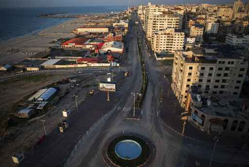 FILE - This Dec. 18, 2020 file photo shows an empty main road in Gaza City.  Qatar pledged $60 million on Thursday, Feb. 25, 2021,  to help construct a natural gas pipeline running from Israel into the Gaza Strip, the Qatari government said, a project that aims to ease the energy crisis that long has afflicted the impoverished Palestinian enclave. (AP Photo/Khalil Hamra, File)